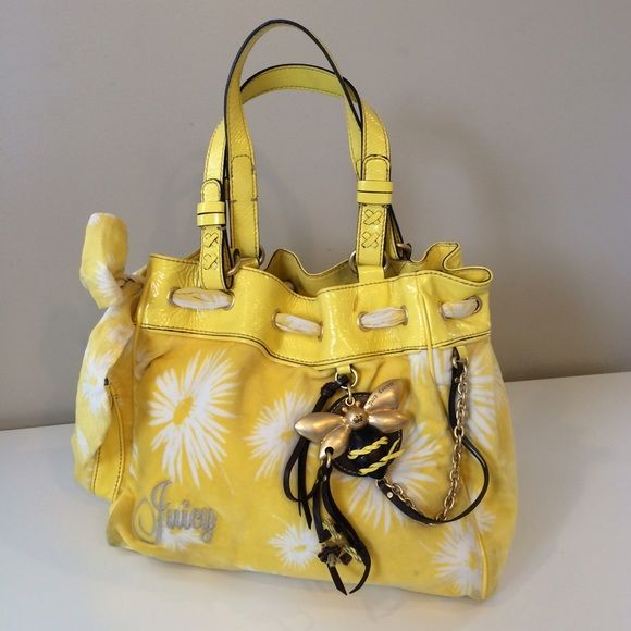 Juicy Couture Daisy Bumblebee yellow Handbag Gently used, this gorgeous bag features soft velour daisy printed fabric, with a darling brass and leather hanging icon logo. Also features patent yellow leather trim. And includes a pretty ruffle bow that can be cinched around the top, or let out, depending on your style. Also includes a magnetic strappy closure and lots of pockets inside as well as a detachable little mirror. Juicy Couture Bags Shoulder Bags