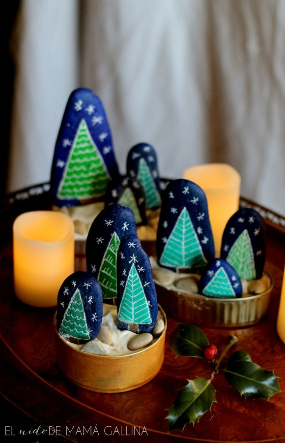 DIY Painted Stone Christmas Tree Forest Tutorial from el nido de mama gallina.Make this pretty DIY Painted Stone Christmas Forest with your kids using cheap supplies like stones, paint, white pens and cans. Photos by el nido de mama gallina, GIF by...