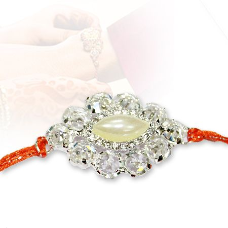 Gift your Brother a Latest Varieties of Designer Rakhi, Vedicvaani.com 2016 latest Collection,Charm Rakhi, artificial gem in centre and silver embellishment.  Designer Rakhi with artificial gem in the center surrounded by silver embellishment. Set in orange thread.