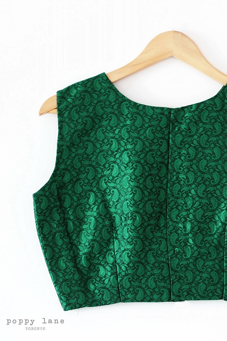 Evergreen -  Sleeveless, crew-neck green brocade blouse. Buttons enclosures down the back. Optional net long-sleeves included. Shop now at poppylane.ca