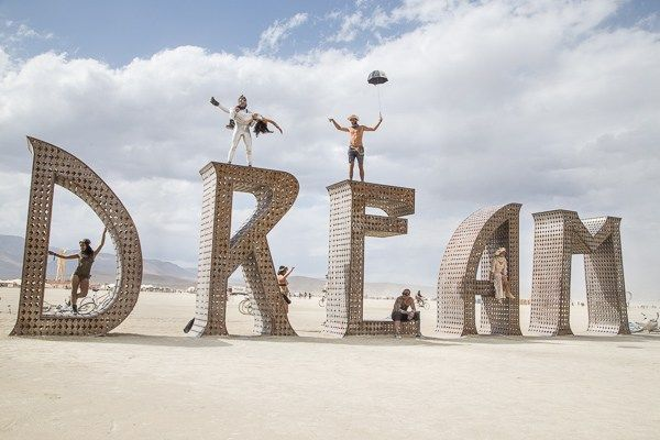 mr and mrs adventure, what is burning man, giant letters, people on top of giant letters, incredible burning man Dream structure, climbing structures at burning man, giant letters, dream art, couple on top of a dream, adventure couple