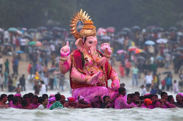 """Devotees carry an idol of Hindu elephant god Ganesh, the deity of prosperity, into the water from Girgaum Chowpatty beach before immersing it in the waters of the Arabian Sea on the last day of the Ganesh Chaturthi festival in Mumbai, on September 11, 2011; symbolizing a ritual send-off of his journey towards his abode in """"Kailash."""""""
