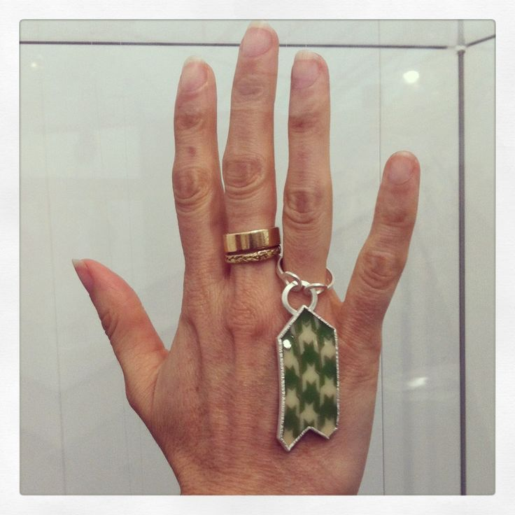 Octavia Cook, Armistice Fling Ring, 2013 - a swinging pendant ring in the form of a herringbone upholstered arrow - modelled by an author from Wellington at Auckland Art Fair