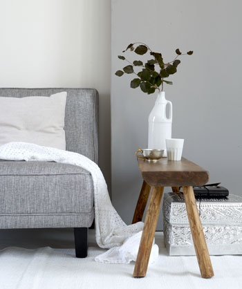 grey sofa rustic wooden stool and white accessories for the modern living room