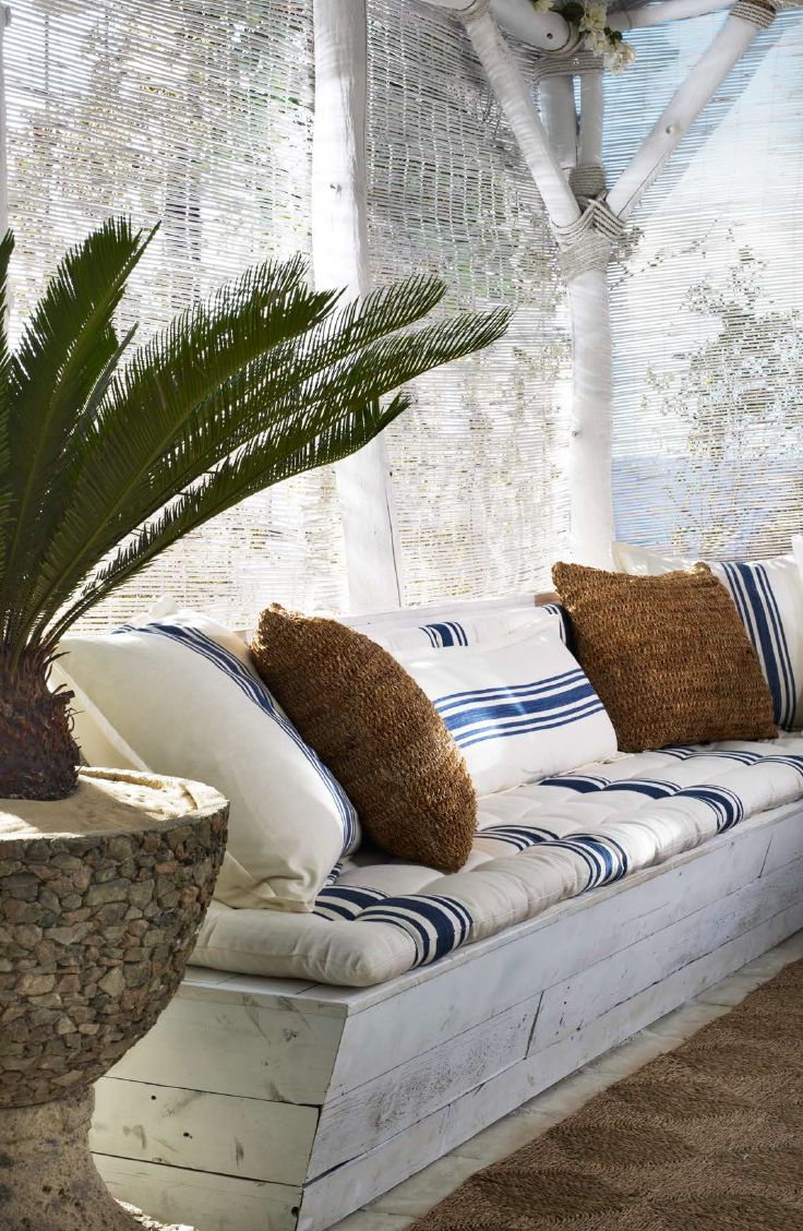 Ralph Lauren Home creates a shady beach retreat with bench cushions and throw pillows sewn from classic blue and white striped textiles.                                                                                                                                                     Mais