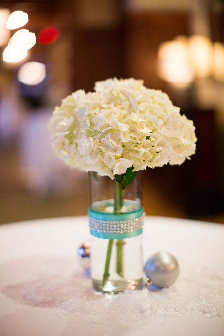 Centerpiece from cocktail hour -- winter wedding white hydrangeas, Tiffany blue ribbon and silver sparkles, with snow and silver ornaments