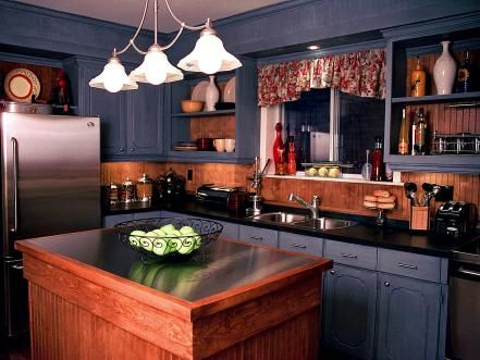 The denim blue cabinets and wooden beadboard backsplash add a punch of warmth to this kitchen. Meanwhile, the stainless steel appliances, accessories and island top add a modern touch to the space, designed by Candice Olson.