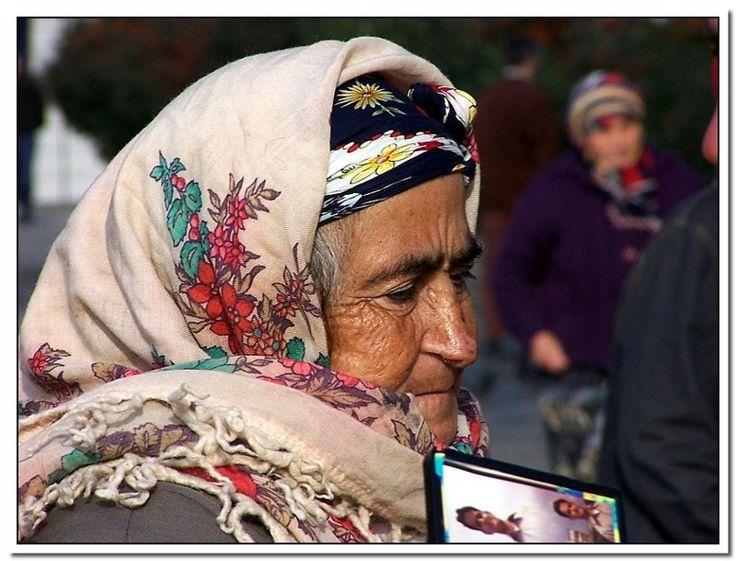 Aisha & 10th Commandment - Beyazit, Istanbul-Bu yaşlı Anadolu kadını, meydandaki çok sayıdaki kuş yemi satıcısından biri. Büyük bir ihtimalle Anadolu'nun ücra bir köşesinden gelmiş buralara ve kuş yemi satarak bu büyük şehirde yaşam mücadelesi veriyor. İstanbul gibi büyük bir şehirde yaşamanın zorlukları yüzündeki çizgilerde okunuyor.  Ama Ayşe'nin bir başka misyonu daha var. O da seneler evvel kaybettiği oğlunu bulmak. Oğlunun resimlerinden birkaçını plastik bir çerçeveye tutturmuş, hep…
