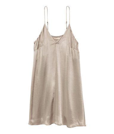 Silberfarben. Kurzes Kleid aus Satin mit schmalen verstellbaren Trägern. Das Kleid hat vorn einen V-Ausschnitt und ist leicht ausgestellt. Ungefüttert.