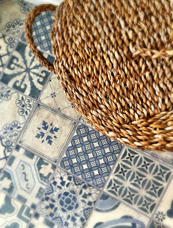 Blue patterned floor tiles and rustic woven laundry bin.