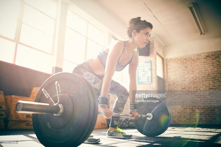 Full length of determined young female deadlifting barbell. Low angle view of woman is looking away. Sunlight is streaming through window.