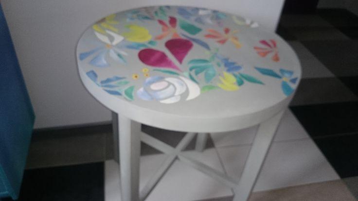 Drewniany stolik w kwiatowej kompozycji .