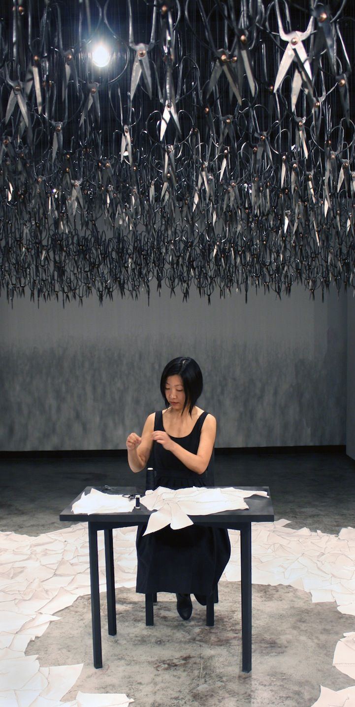 Imagine walking into a silent room where a woman is mending. Now imagine that she's sitting underneath 1,500 pairs of sharp Chinese scissors that are suspended from the ceiling, precariously pointed downwards. This was the idea behind The Mending Project by Beili Liu.