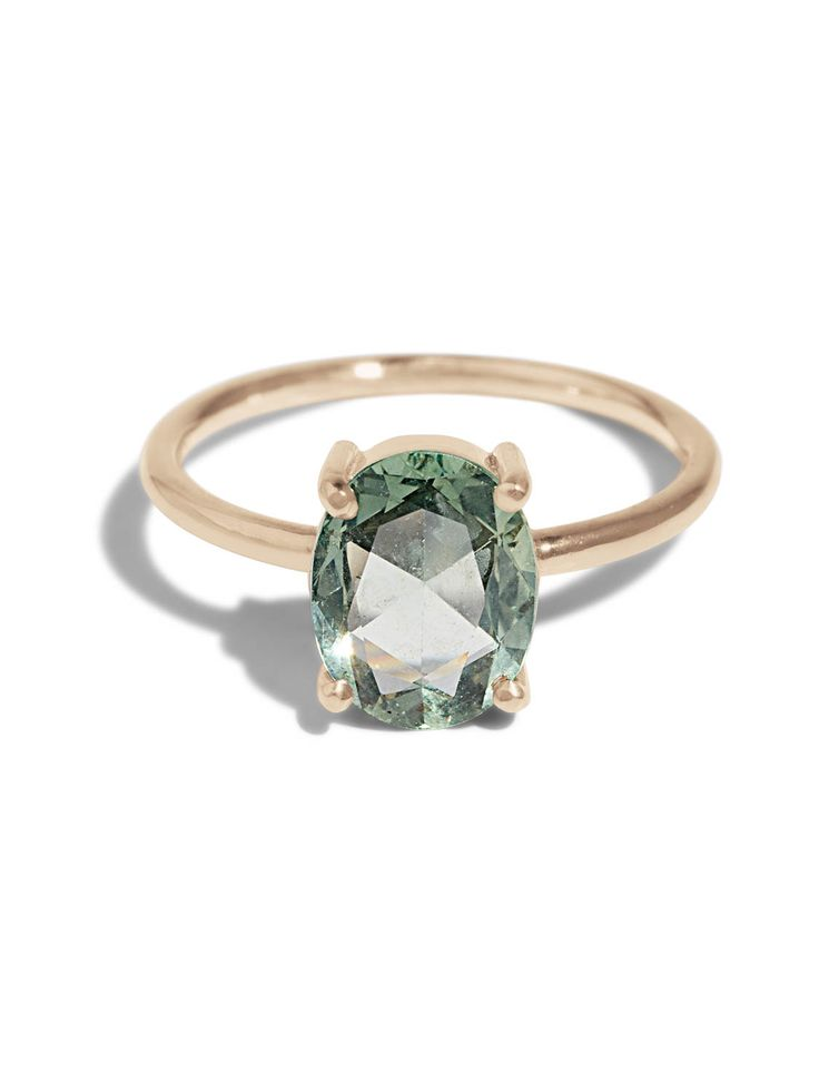 The Custom Rosecut Ring showcases a distinctive green rose cut sapphire in a delicate 14kt yellow gold prong setting.
