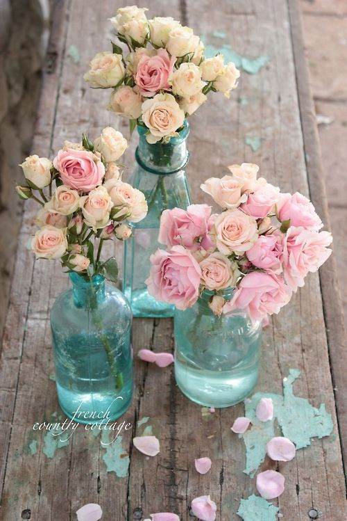Antique roses arranged in vintage blue bottles make a lovely centerpiece on a rustic table.