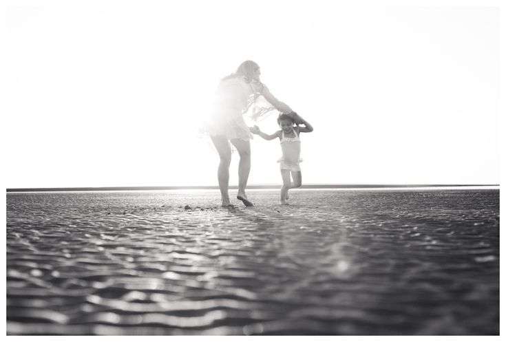 Black and white image of mother and daughter spinning on the beach in Tamarindo, Costa Rica. Photographed by Kristen M. Brown, Samba to the Sea Photography.