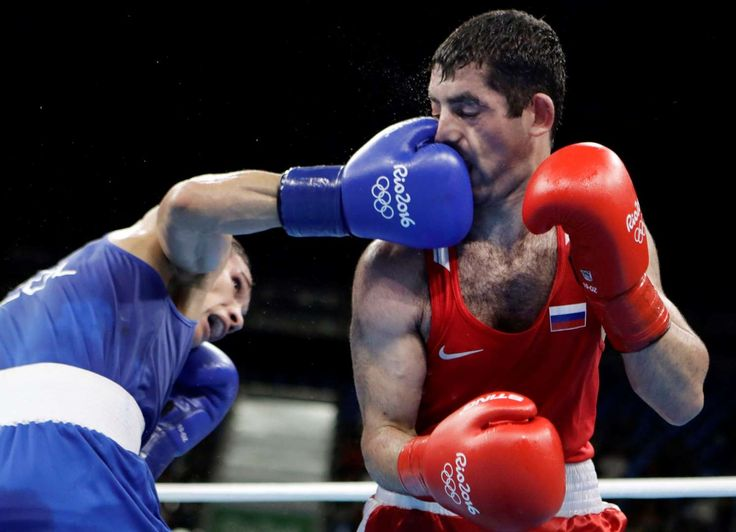 Taking a punch:    Colombia's Ceiber David Avila, left, lands a punch on Russia's Misha Aloian during a men's flyweight 52-kg quarterfinals boxing match on Aug. 17.