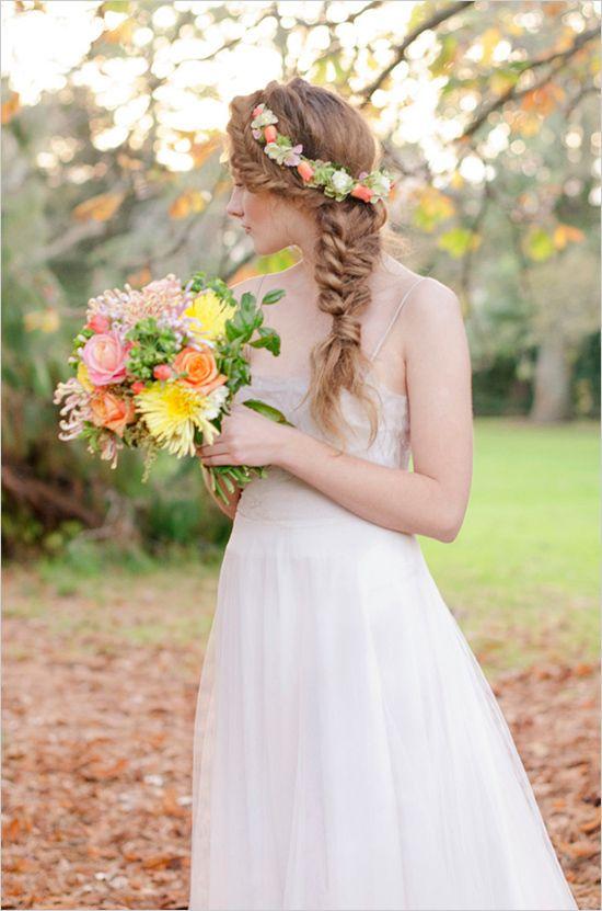 Si no quieres peinarte de moño el día de tu boda, esta idea de trenza con corona de flores está estelar.