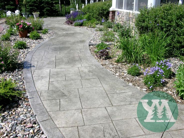 A curved concrete walkway is stamped with a natural stone pattern - Yardmasters Landscapes