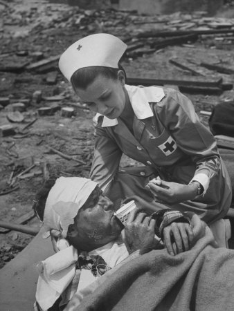 The Red Cross Nurse Trying to Help the Injured Man Eat and Drink Lámina fotográfica de primera calidad