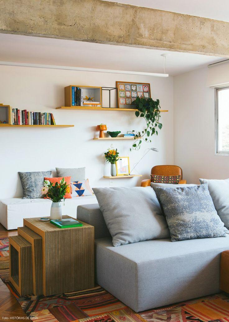 Sala de estar aconchegante com sofá cinza, piso de taco de madeira e vigas de concreto.