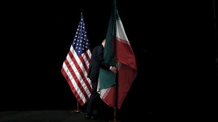Un miembro de la organización retira la bandera de Irán del estrado durante las conversaciones sobre el programa nuclear iraní en Viana. 14 de julio.