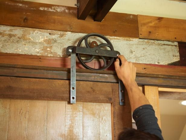 Stand the door on the shim and, with a helper, lay the wheels on the track, noting the correct locations for the final lag bolts from the strap to the door.