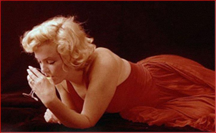 Marilyn. Red dress sitting. Photo by Milton Greene, 1957.