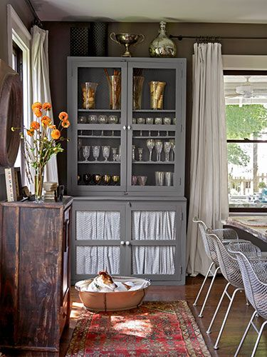 """Adopt a smart strategy for storage: """"I like to keep plates and glasses in the dining room for easy access,"""" says Susan. """"But that means it all has to look good."""" In addition to painting her hutches with Behr's Pier and replacing the glass panels with chicken wire, she devised a way to conceal clutter by staple-gunning drop cloth inside the lower doors. """"The material is cheap,"""" she admits. """"Plus, once you wash it, the coarse cotton drapes beautifully."""""""