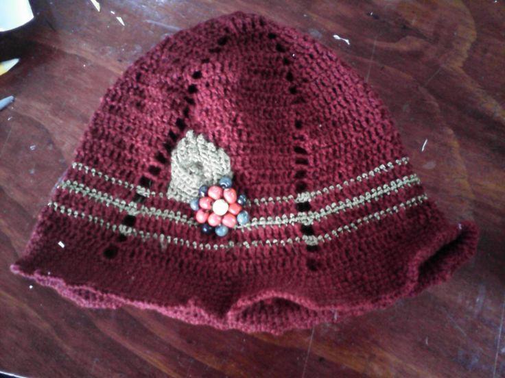 Sombrero estilo cloche, tejido en hilo de algodon granate y lurex bronce. Bordado con cuentas de madera.