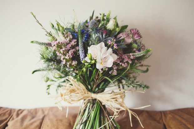 A large domed bouquet tied with raffia - astrantia, Veronica, wax flower, lizzies, herbs