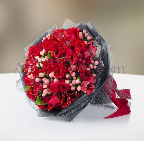 Hand bouquet of 20 red roses with seasonal flowers.