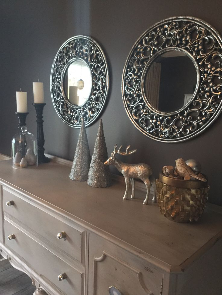 Mixing Rustic and Glam....a distressed sideboard is highlighted with gleaming knobs from Anthropologie, and the mix of metals adds interest to the room!