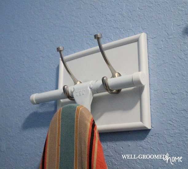 """Laundry Room Organization - Well-Groomed Home """"I made an ironing board holder out of some scrap wood and an old picture frame.  I simply painted it to match our wood trim and secured a bracket to the wall behind the frame for extra support.  Then I took coat hooks, purchased from Walmart, and attached them to the front of the wood in the frame."""""""