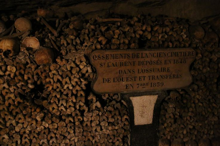 The signs say which cemetery the remains had originally been buried in. Paris Catacombs.