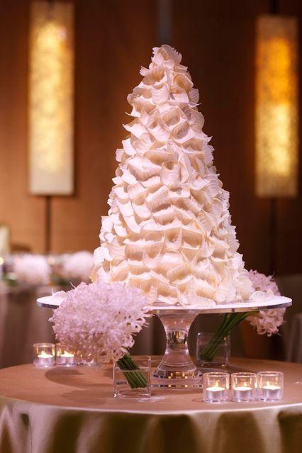 ゲストみんなの目を釘付けにするグランド ハイアット 東京のベリー×ホワイトチョコケーキ。ホテル内にあるチャペルの柱に見立てたというロールチョコレートを周囲にアレンジ、ベリーをたっぷりとあしらったデザインに胸がキュン。見た目にもスタイリッシュなケーキは洗練された大人のウェディングを演出してくれる。 天使の羽根をイメージして軽やかなホワイトチョコレートをあしらったトライアングルフォ...