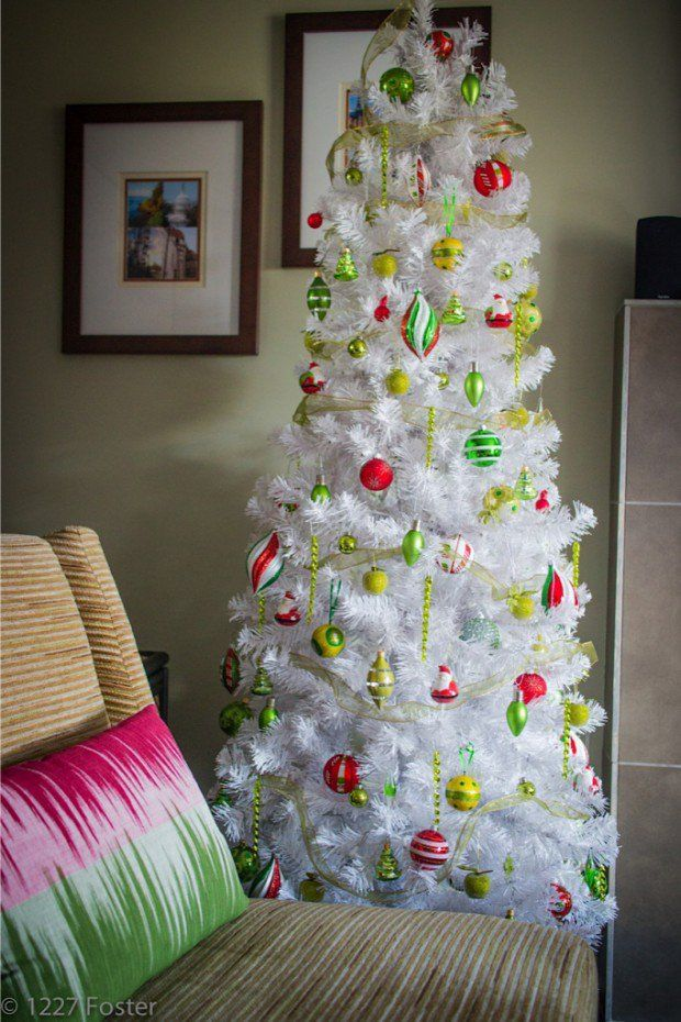 Snow white Christmas tree accented with shades of green and red for a  whimsical theme.reminds me of a grinch style tree