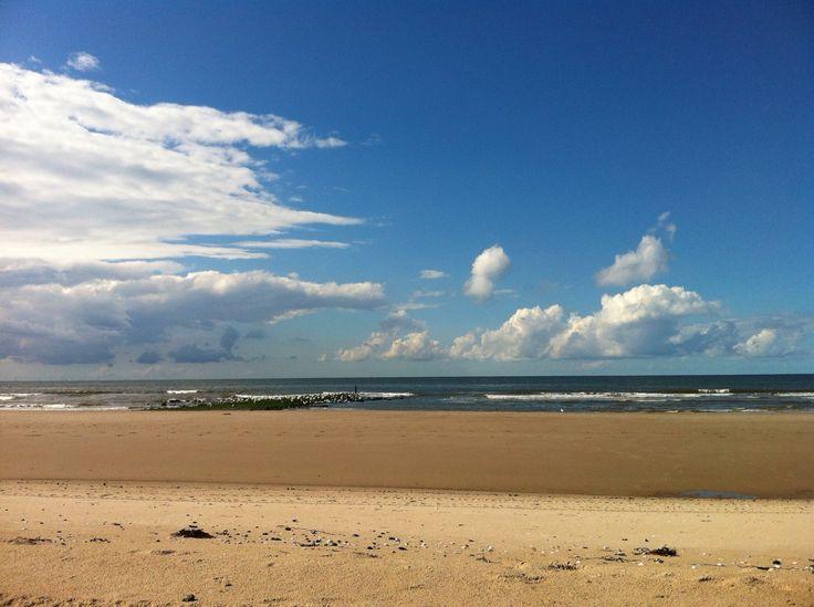 zonnig strand met opkomende wolken