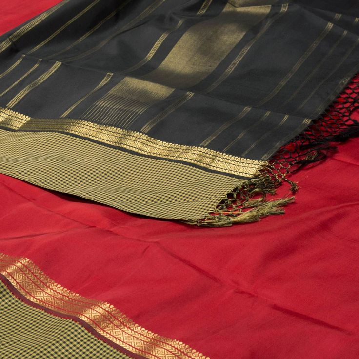 "The ""Red"" #handwoven #Kanjivaram #Silk #Sari from Parisera is set off by a #gold #zari and checkered border on either side. An attractive gold zari adorn the black pallu. The border is repeated on the brocade black blouse that completes the sari."
