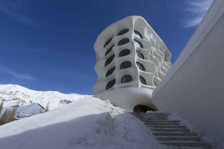 "Just an hour outside of Tehran looms the Barin Ski Resort, a white fortress designed to mimic the snow-covered mountains that surround it, and with an interior that feels an awful lot like an igloo (though the architects opted for ""topographic layers"" instead of ice blocks). The Barin Ski Resort was designed, inside and out, to reflect and complement its natural surroundings, and the effect is truly stunning."