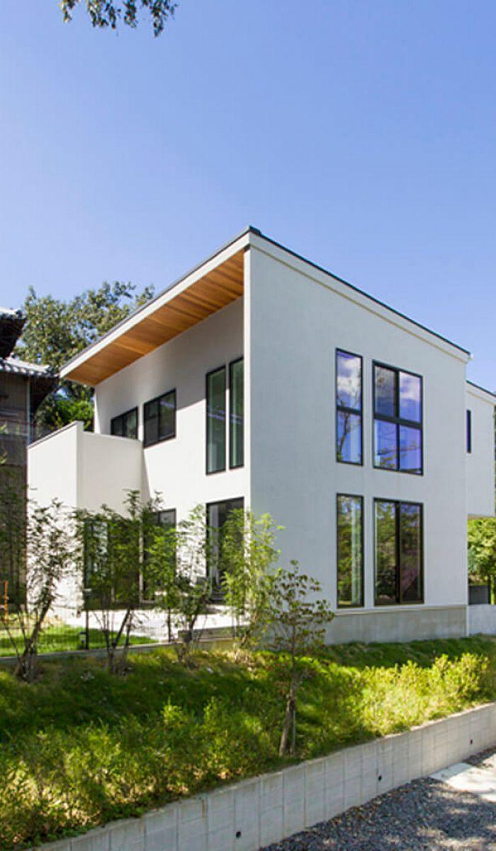 大きな窓が印象的な白い外観デザインは 周辺に広がる緑にも映える 軒