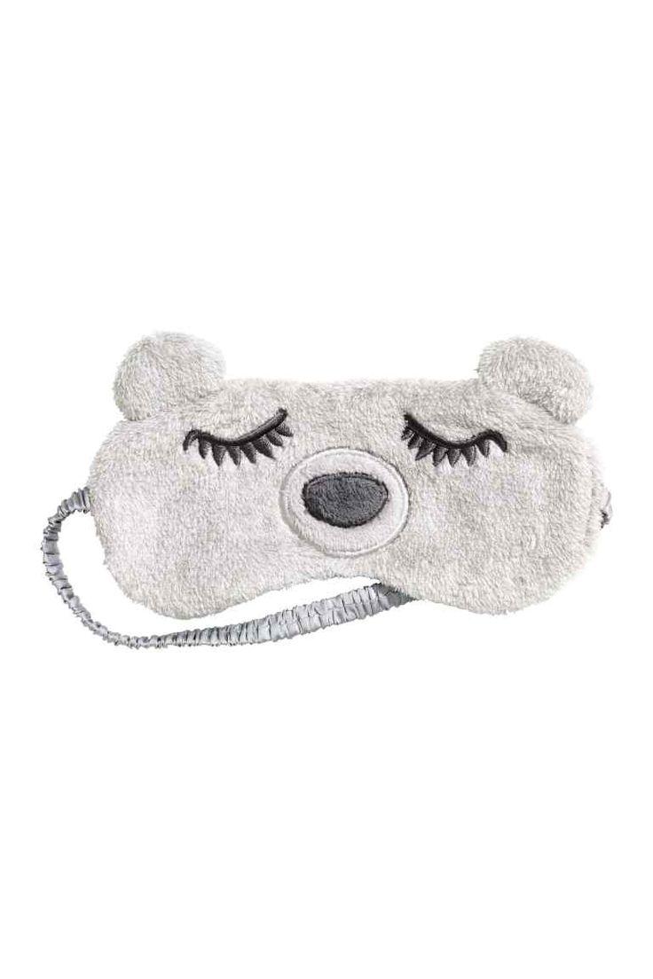 Masque de sommeil: Masque de sommeil en tissu peluche matelassé avec dos en satin. Modèle avec broderies devant et élastique habillé. Garnissage polyester. Dimensions 9x20 cm environ.