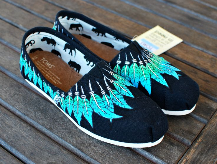 This pair of native american indian style moccasin toms shoes feature light blue and green feathers hanging around the rim of the shoe in a moccasin fashion. These Moccasin TOMS shoes are made to orde