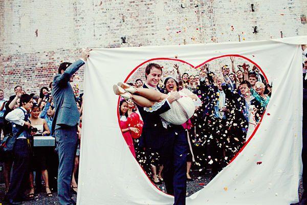 """Melle Dentelle a de belles idées pour la sortie de cérémonie : """"le marié prend sa belle dans ses bras, et en la portant, il franchit un drap découpé d'une forme de cœur. [...] vous pouvez franchir le grand cœur main dans la main.Et pendant ce temps, les invités ne se privent pas de lancer plein de confettis !"""""""