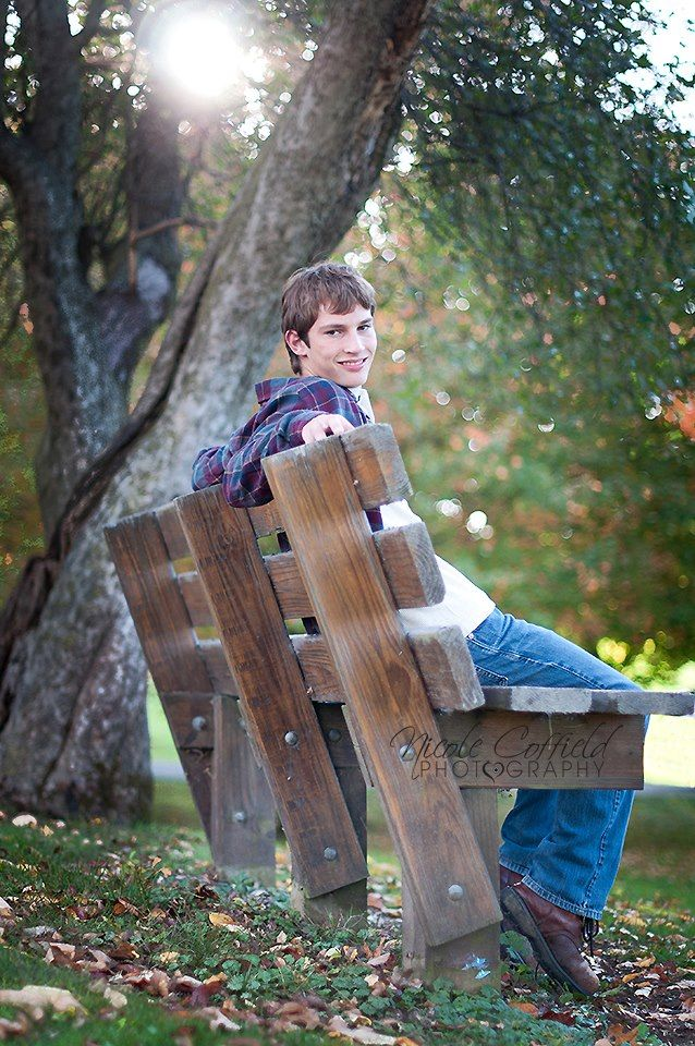 senior boy pose on park bench - fall sunflare
