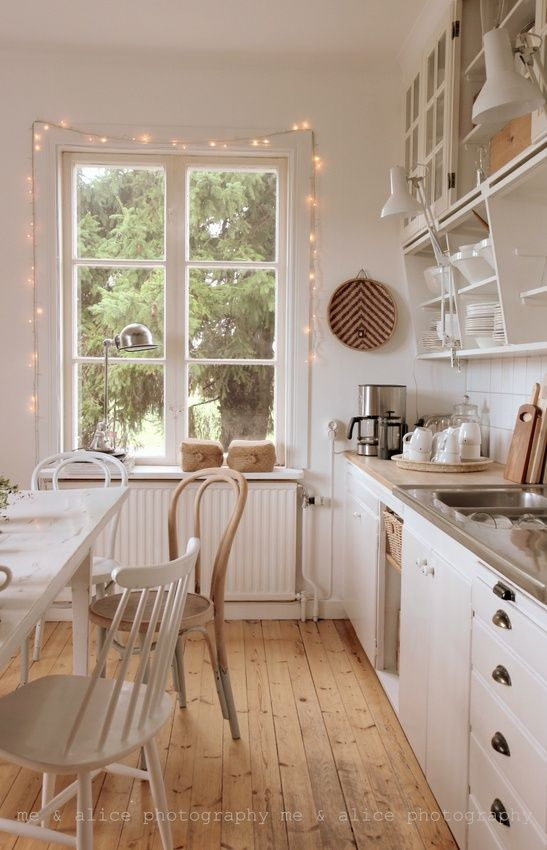 White kitchen + wood floors Cottage feel and i love the lights around the window