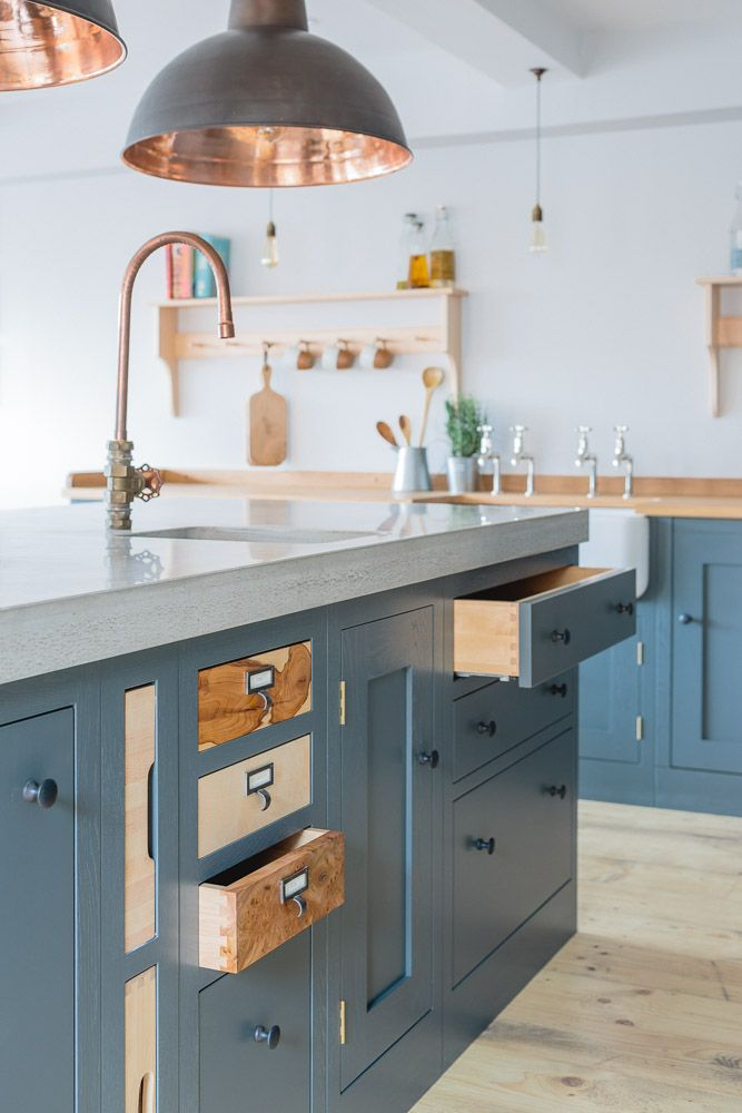 Industrial Shaker Style showroom kitchen with oak cabinetry. The base cabinets are hand painted in Farrow & Ball Down Pipe and have an oak worktop. The shelving is a birch shaker peg shelf and open oak drawers are visible below. The island has a polished concrete worktop and the Shaw's farmhouse sink with double Perrin & Rowe taps that offset the colours beautifully. The wood inlay drawers are yew, sycamore, and walnut. Hanging pendant lights are from Original BTC.