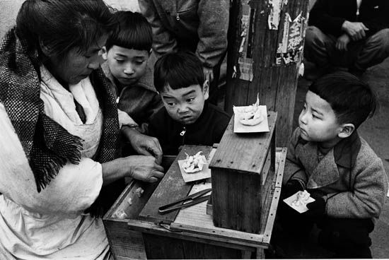 Asakusa, Tokyo, 1954 by Ken Domon. Boys watching cashier.