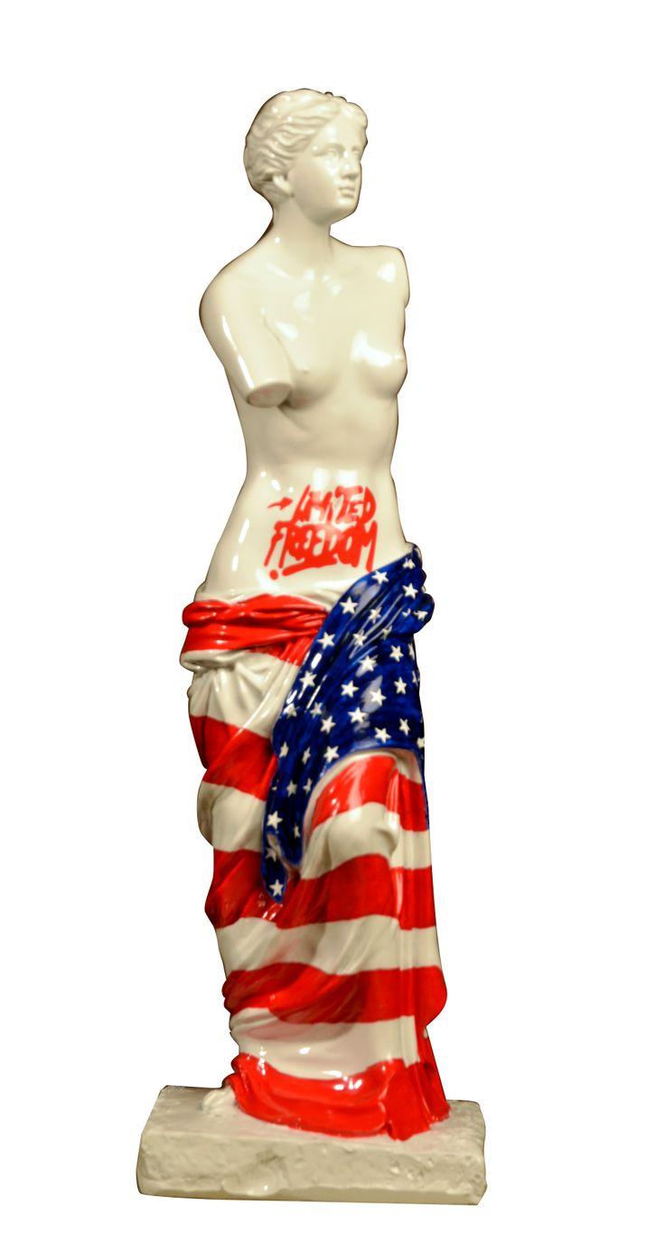 Venus Independance Day Tribute to USA Le drapeau américain se compose de 13 bandes rouges représentant les états fondateurs qui se sont unis pour former les Etats-Unis d'Amérique.  Ces bandes sont cousues l'une à l'autre pour symboliser l'union ainsi scellée entre les états.  Notre Venus en a fait sa tunique ! Venus en résine de 43 cm de hauteur hhttp://boutique.ohlavachebleue.fr/vb/