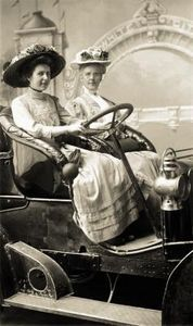over-sized, embellished hats and decorated bonnets were popular in the late 1800s - posing in a horseless carriage